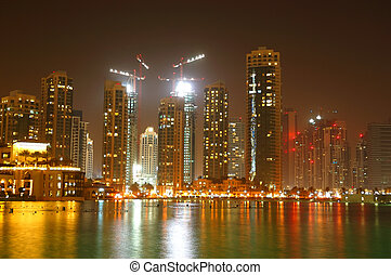 New skyscrapers at Dubai Downtown and man-made lake in night illumination, UAE