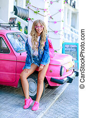 New stylish girl with denim jacket near the pink car with a pink bag.
