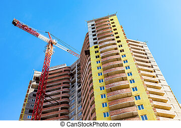 New tall apartment building under construction with crane against blue sky background