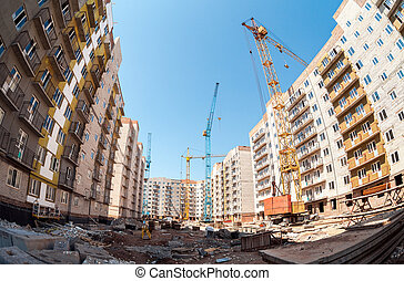 New tall apartment buildings under construction with cranes against blue sky background
