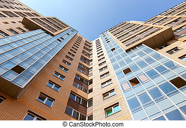 New tall modern apartment building against blue sky background