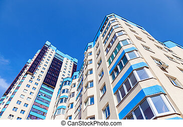 New tall modern apartment buildings against blue sky background