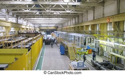 New train stands in plant workshop near platform, time lapse