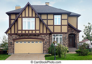 New two-storied brown stone cottage with beige garage and roof.