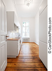 new white kitchenette / kitchen in renovated old building with wooden floor