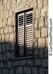 New window with shutters on stone wall