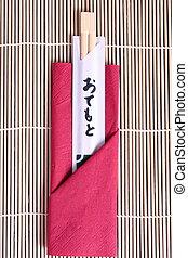 new wooden chopsticks laying on bamboo mat