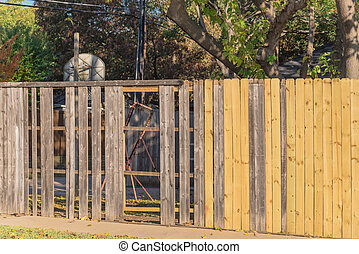 New wooden fence near collapsed slats in backyard of residential house with mature trees in suburban Dallas, Texas