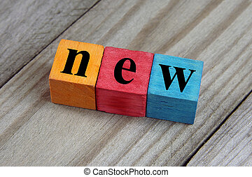 new word on wooden colorful cubes