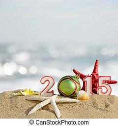 New year 2015 sign with seashells, starfish and christmas ball on a beach sand