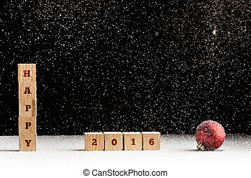 New Year 2016 background with falling snow and a red Christmas bauble with the word Happy spelled out on stacked wooden blocks