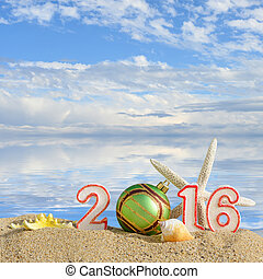 New year 2016 sign on a beach sand with seashells, starfish ...