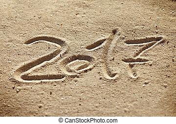 New year 2017 written on sand
