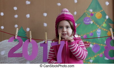 New Year 2018 concept. Beautiful small girl decorating the New Year numeral. background of a painted Christmas tree and snow