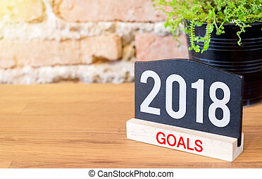 New year 2018 goals on blackboard sign and green plant on...