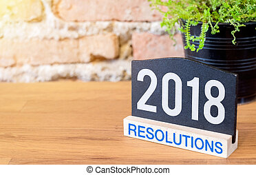 New year 2018 resolutions on blackboard sign and green plant...