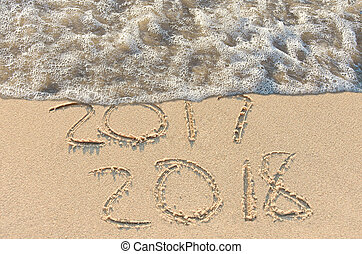 New Year 2018 text on beach with frothy water edge