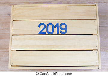 Blue symbol with number 2019 on a wooden background