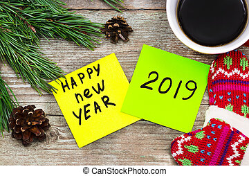 new year 2019 - handwriting in black ink on a sticky note with a cup of coffee and mittens, New Year resolutions concept