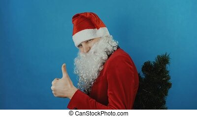 New year 2019, man like a Santa holds a Christmas tree behind his back and shows thumb up like, blue background