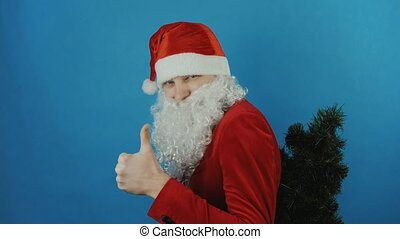 New year 2019, man like a Santa with a Christmas tree shows thumb up like, on blue background