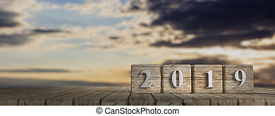 New year 2019 on wooden cubes, wooden table, sunrise background, banner, copy space. 3d illustration