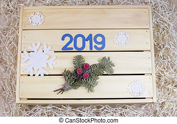 Symbol from number 2019 and spruce twig on a wooden background with snowflakes