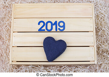New Year 2019. Symbol with and a heart on a wooden background