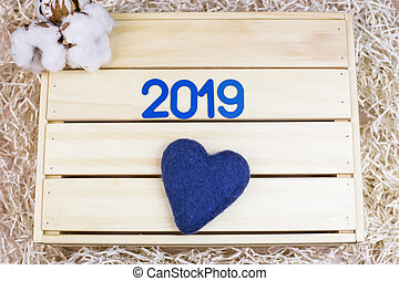 Symbol with number 2019 and cotton on a wooden background.