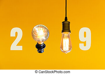 New year 2019 with vintage light bulb on orange background