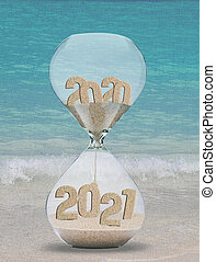 New Year 2021 sand hourglass on tropical beach background