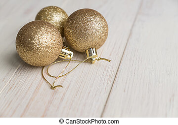New year and Christmas background - three golden balls on wooden background.