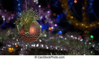 New Year and Christmas decorations. Burning candles. Flashing Garlands. Blurred background. A beautiful red ball.