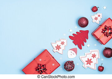 New Year and Christmas frame. Red and white christmas decorations - gift boxes, stars, christmas tree, Santa Claus on pastel blue background. Top view, flat lay, copy space