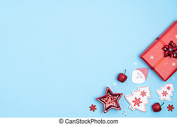 New Year and Christmas frame. Red and white christmas decorations -gift boxes, stars, christmas tree, Santa Claus on pastel blue paper background. Top view, flat lay, copy space