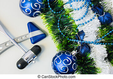 New Year and Christmas in the office of a neurologist, neurosurgeon or neuroscientist. Two neurological hammer lying next to a Christmas tree decoration