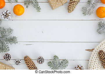 New year background. Xmas, merry christmas frame from decorations, fir cones and branch, knitted scarf, gift box, orange mandarin on white wooden planks table Top view. Trendy hand mande design mockup