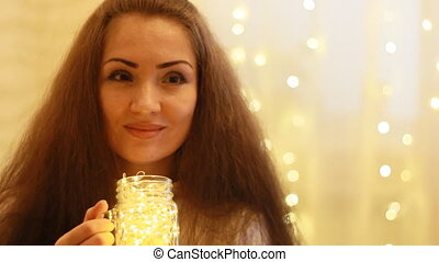New Year. Christmas. Beautiful woman holds in hands a lamp,...
