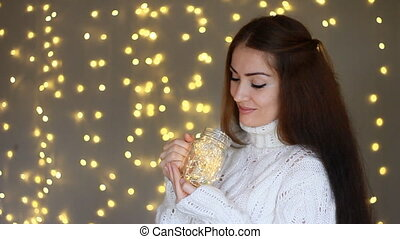 New Year. Christmas. Beautiful woman in a warm white sweater...
