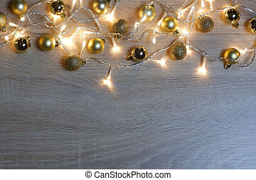 New year christmas composition from golden shiny and matte balls on light oak wood background with copy space