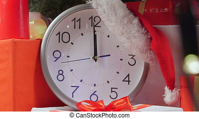 New Year clock ticking under Christmas tree showing few...