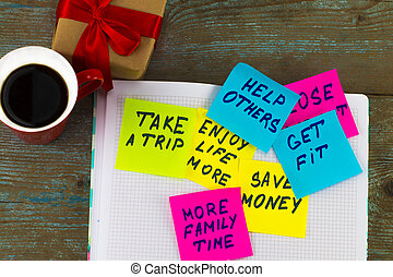 new year goals or resolutions - colorful sticky notes on a Notepad with coffee Cup