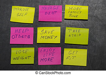 new year goals or resolutions - sticky notes on a blackboard