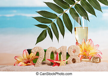 New Year inscription 2018, bottle and glass of champagne decorated with flowers and leaf, starfish in the sand on beach.