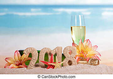 New Year inscription 2018, bottle and glass of champagne decorated with flowers, starfish in the sand on beach.