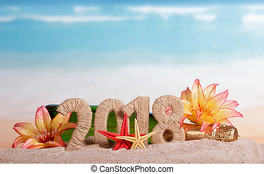 New Year inscription 2018, bottle of champagne decorated with flowers, and starfish in the sand on the beach.