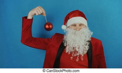 New year, man like a Santa Claus with Christmas red ball bauble toy, on blue background