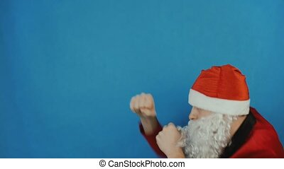 New year, man like a Santa is boxing and throws punches by his fists, Christmas 2019, on blue background