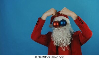 New year, man like a Santa with red and blue Christmas balls baubles toys, on blue background