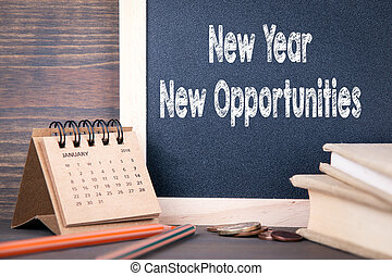 new year new opportunities. paper calendar and chalkboard on a wooden table